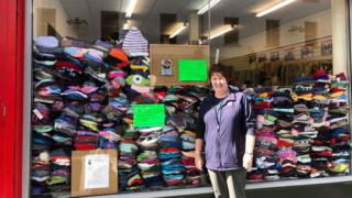 Doreen Armstrong pictured outside the Salvation Army shop in Ballymena and over 3,000 woolly hats