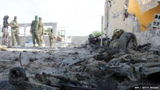Somali soldiers stand next to the site where Al Shebab militants carried out a suicide attack against a military intelligence base in Mogadishu 21 June 2015