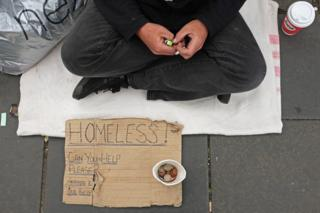 Hands, sign and money cup belonging to a homeless man