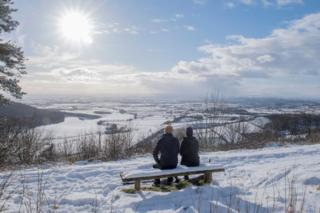 A couple sit on a bench overlooking the snow-covered fields of Thirsk at Sutton bank National Park Centre in the North Yorks Moors National Park in North Yorkshire