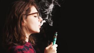 Young woman wearing glasses and smoking an e-cigarette.
