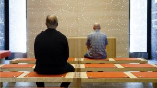 شخصان جالسان على مقاعد داخل قاعة ويصليان