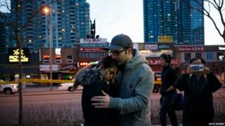 People embrace at the scene of a memorial for victims of a crash at Yonge St. at Finch Ave.