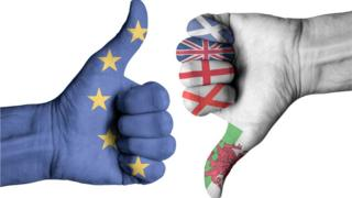 UK flags and EU flag on human hands