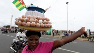 Jeune revendeuse d'œufs bouillis avec un drapelet togolais au-dessus de sa marchandise posée sur sa tête