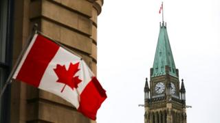 Canadian Flag on top building for Ottawa across from di Peace Tower for Centre Block of Parliament Hill.