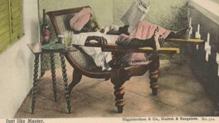A picture postcard of an Indian man reading a newspaper while relaxing on a chair