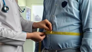 Médica mede cintura de paciente com fita métrica