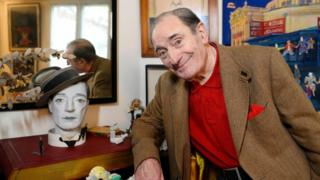 Pierre Etaix poses for a photo beside a face mask in his home
