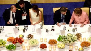 Russia's President Vladimir Putin, US First Lady Melania Trump, Argentina's President Mauricio Macri, German Chancellor Angela Merkel attend the banquet after a concert at the Elbphilharmonie concert hall during the G20 Summit in Hamburg, Germany, on July 7, 2017. Leaders of the world's top economies will gather from July 7 to 8, 2017 in Germany for likely the stormiest G20 summit in years, with disagreements ranging from wars to climate change and global trade