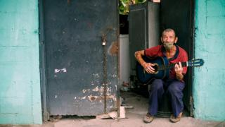 A man wearing a protective mask plays the guitar at his front door in Mejicanos, San Salvador, El Salvador - 7 May 2020