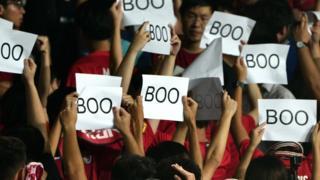 """有一些观众则举起印有""""Boo""""字样的纸片,并在奏国歌时背向球场。"""
