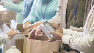 Mãos de pessoas seguram alimentos e mexem em caixas, indicando local de doação de alimentos