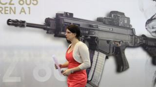 A woman passes a picture of an CZ-805 assault rifle at the booth of Czech firearm producer Ceska Zbrojovka during the International Exhibition of Defence and Security Technologies (IDET) in Brno, Czech Republic (22 May 2013)