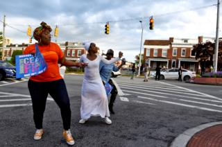 """People dance in the street while holding signs that read """"ceasefire"""" in Baltimore. Ceasefire is a local organization that stages events to call attention to the gun violence in Baltimore"""