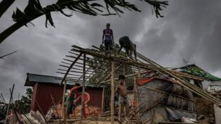 Men rebuilding a hut
