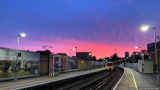 Red sunrise by a train platform