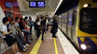 Passengers wait on a platform at Melbourne Central train station
