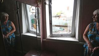 Жінка дивиться в розбите вікно