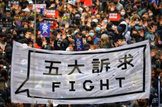 "People hold a banner reading ""Fight"" as they take part in an anti-government rally on New Year's Day in Hong Kong"