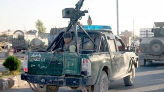 An Afghan policeman travels on a pick up truck in the embattled city of Tarin Kot