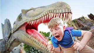 An animatronic dinosaur and a child at Mighty Claws Adventure Golf in Bournemouth