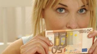فتاة تمسك بورقة نقدية