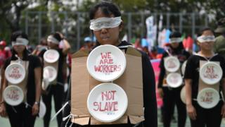Migrant workers are seen wearing blindfolds and wearing cardboard signs during the May Day rally in Hong Kong