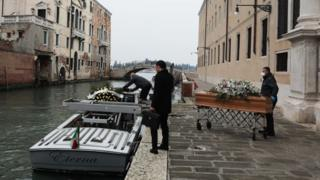 Undertakers place coffins on a boat in Venice
