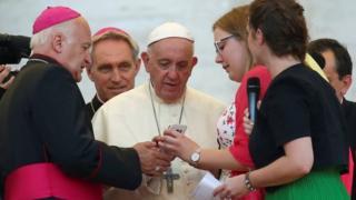 Seorang pendeta menunjukkan telepon genggam kepada Paus Fransiskus