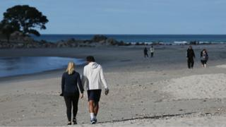 People walking on a beach in New Zealand