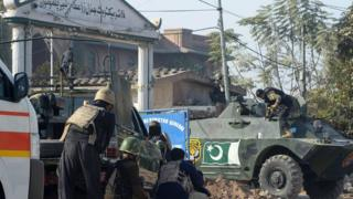 Pakistani security personnel take position outside an Agriculture Training Institute after an attack by Taliban militants in Peshawar on 1 December 2017.