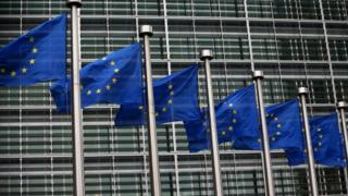 EU flags waving outside European Commission building in Brussels