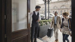 A young hotel doorman welcomes guests to a hotel