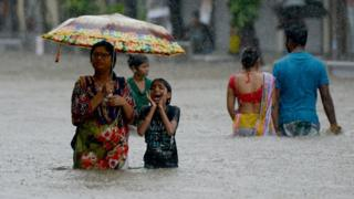 Indians wade through a flooded street during heavy rain showers in Mumbai on August 29, 2017