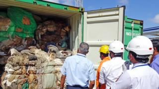 In this handout picture provided by Sri Lankan Customs on July 23, 2019, customs officials inspect the load of a container at a port in Colombo