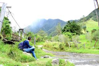 Hombre joven sentado al pie de una carretera mirando hacia el horizonte