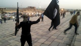 IS fighter holds a flag of the group and a weapon on a street in Mosul