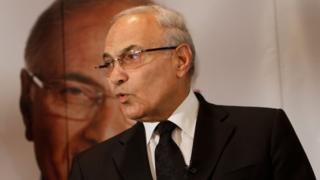 Ahmed Shafiq, pictured in a dark suit and tie in front of a large photo of his own face, in a 2012 photo