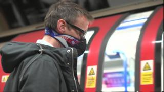 Man wearing a dust mask on Tube