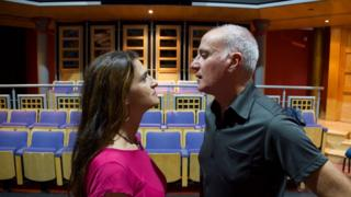 A woman and a man stare each other down, nose to nose, in a theatre rehearsal room