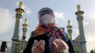 in_pictures A worshipper in Tehran, Iran wears protective equipment