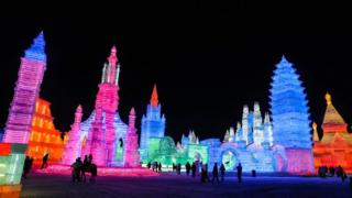People visit ice sculptures illuminated by coloured lights at the Ice and Snow World during the annual Harbin International Ice and Snow Sculpture Festival on 4 January 2019