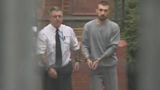 Denis Erdinch Beytula in handcuffs with a prison officer