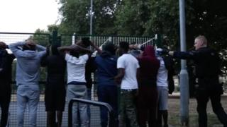 A group being stopped by armed police