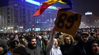 A man holds a placard reading '89' , the year of the Romanian uprising in 1989 which toppled late dictator Nicolae Ceausescu as people demonstrate in front of government headquarters against controversial decrees to pardon corrupt politicians and decriminalise other offenses on 31 January 2017 in Bucharest