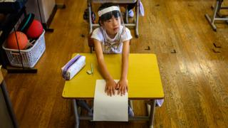 School pupil in Japan wears a face shield