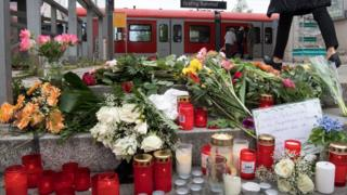 A condolence note, flowers and candles placed at the entrance to the railway station in Grafing near Munich, Germany, 11 May 2016.