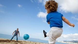 A child plays football with his father at Can Pere Antoni Beach in Palma de Mallorca, on April 26, 2020 during a national lockdown to prevent the spread of the COVID-19 disease.