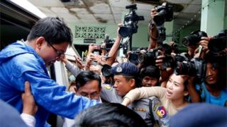 Reuters reporter Wa Lone's wife Pan Ei Mon (2nd-R) tries to catch his hand as he arrives at court in Yangon, Myanmar, 27 December 27, 2017.